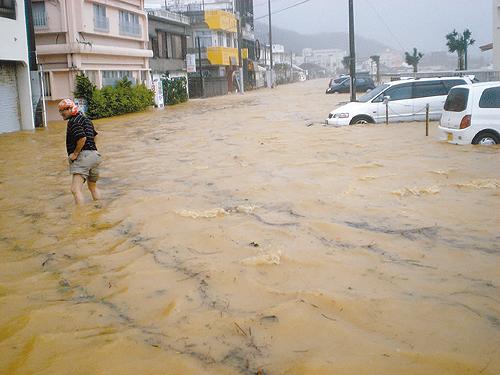 道路が冠水し家屋や車両に被害が出た=16日午前7時20分ごろ、本部町渡久地(比嘉貴哉通信員撮影)