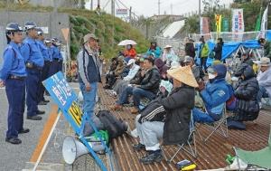 ゲート前の山型鉄板の上で抗議の声を上げる市民ら=14日午前8時40分ごろ、名護市辺野古の米軍キャンプ・シュワブ