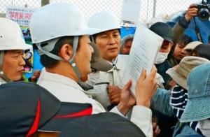 座り込みを続ける市民らにテント撤去を求める文書を読み上げる沖縄防衛局の職員(左から2人目)=19日午後4時15分、名護市辺野古のキャンプ・シュワブ新ゲート前(花城克俊撮影)