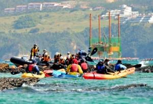 ボーリング調査が続くスパット台船を海上で監視するカヌー隊(手前)=24日午前10時すぎ、名護市辺野古(伊藤桃子撮影)