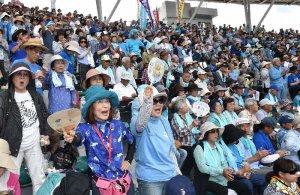 ステージの新基地建設反対の歌に合わせて合唱する大会参加者=17日午前、沖縄セルラースタジアム那覇