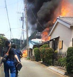住宅に墜落し炎を上げる小型機(中央)=26日午前、東京都調布市(住民提供)