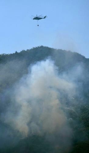 名護市の米軍キャンプ・シュワブ内で発生した山火事の消火に当たる米軍ヘリCH53=13日午後2時27分ごろ
