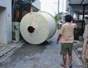 強風で飛ばされた水タンク=午前10時26分ごろ、石垣市大川(新崎哲史撮影)