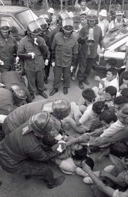 都市型訓練施設建設に反対して座り込む住民を排除する機動隊員=1989年10月、恩納村