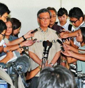 大勢の報道陣に囲まれ質問に答える翁長雄志知事(中央)=8日午後、那覇空港
