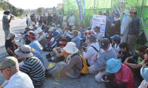 米軍キャンプ・シュワブのゲート前に座り込む市民ら=15日午前、名護市辺野古