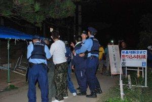 警察官に抑えられる人たち=20日午前1時前、名護市辺野古の米軍キャンプ・シュワブゲート前