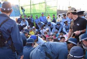 工事車両の進入を阻止しようと座り込む市民と、排除する警官=23日午前7時2分、名護市辺野古の米軍キャンプ・シュワブ旧ゲート前