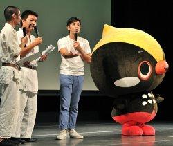 国頭村のキャラクター・くーやん(右)と舞台に立つ監督のゴリさん(右から2人目)=4日午後、那覇市久茂地・タイムスホール