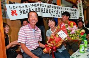 多和田真三郎投手が西武から1位指名され笑顔を見せる父真次さん(手前)と母もと子さん=22日午後5時20分、中城村北浜