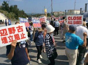 米軍キャンプ・シュワブゲート前で新基地建設反対の声を上げる参加者ら=26日正午ごろ、名護市辺野古