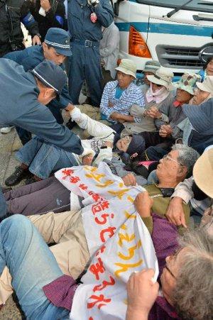 米軍キャンプ・シュワブゲート前で工事車両の進入を阻止しようと集まった市民を排除する警察官=29日午前7時、名護市辺野古