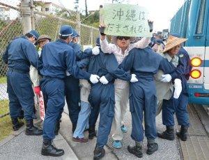機動隊に拘束されても、プラカードを掲げ続ける男性=31日午前7時17分、沖縄県名護市辺野古