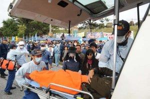 テント前のもみ合いの後、車道に倒れ込み、救急車に運び込まれる市民=4日午前9時23分、名護市辺野古のキャンプ・シュワブ前
