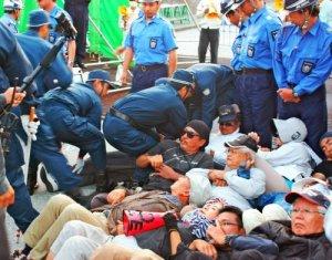 米軍キャンプ・シュワブゲート前で座り込む市民を強制排除する機動隊員ら=19日午前7時すぎ、名護市辺野古