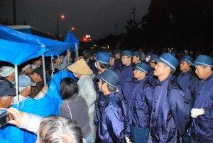 工事車両の進入を阻止しようとゲート前で抗議する市民ら(左)と、退くように求める機動隊ら=3日午前6時50分ごろ、名護市辺野古・米軍キャンプ・シュワブのゲート前