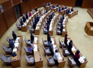 抗告訴訟提起の議決案に起立し賛成の意思を示す県議ら=18日、沖縄県議会