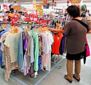 半袖の夏物衣類を品定めする買い物客=那覇市上間のサンキマルエー