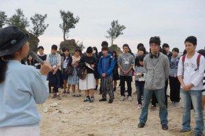 大浦湾を望む瀬嵩の浜で、地域に住む渡具知智佳子さん(左)から話を聞く高校生たち=名護市瀬嵩