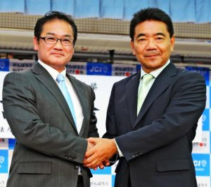 公開討論会で握手を交わす佐喜真淳氏(左)と志村恵一郎氏=26日午後、宜野湾市野嵩・ジュビランス