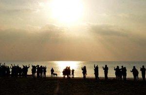 初日の出を望み参加者が輪になって歌い、踊った=1日8時すぎ、名護市辺野古の浜