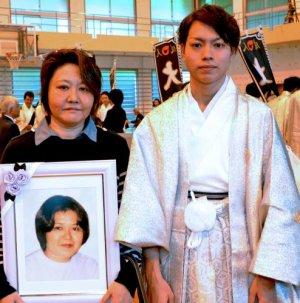 成人式を迎えた崎山星斗さん(右)。伯母のめぐみさんが母おさみさんの遺影を抱いて出席した=4日、大宜味中学校