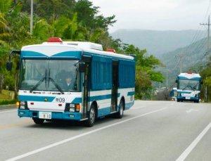 機動隊員を乗せて名護市内を走る警視庁の大型バス=5日午後4時半ごろ