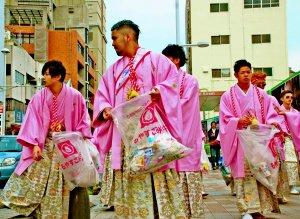 袋を片手に国際通りのごみを拾う石嶺中学出身の新成人ら=10日、那覇市・国際通り