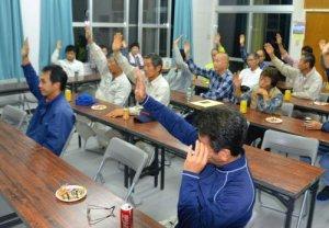 挙手で自衛隊配備反対の意志を示す嵩田地区の住民=10日、石垣市・嵩田公民館