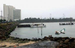 沈んだ船などが放置された「仮設避難港」。奥にはラグナガーデンホテル(左)や海浜公園があり、本島西海岸のリゾートはここで分断されている形だ=宜野湾市真志喜