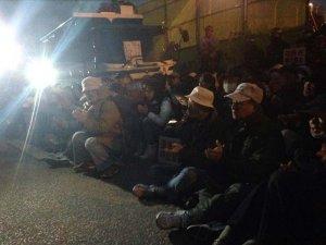 新基地建設の作業車両を止めようと座り込む市民ら=21日午前7時ごろ、名護市辺野古の米軍キャンプ・シュワブゲート前