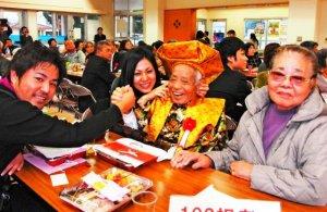 祝福を受け笑顔の蒲戸さん(右から2人目)と、娘のスエ子さん(右)、孫の(左から)新さん、公子さん=読谷村の長浜公民館