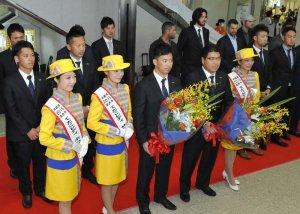 てだこレディーから歓迎の花束を受け取る真中満監督(前列右から2人目)と雄平選手(同左隣)=30日午後、那覇空港