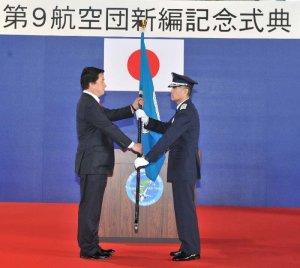 防衛省の若宮健嗣副大臣(左)から指揮官旗を授与される川波清明第9航空団司令=31日午前、航空自衛隊那覇基地
