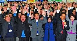 2期目の当選が確実となり、支持者と万歳三唱をする佐喜真淳氏(中央)=24日午後、宜野湾市野嵩の選対事務所