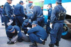 キャンプ・シュワブゲート前で座り込み抗議をする市民を排除する機動隊員=8日午前7時12分、名護市辺野古