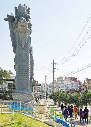 ビニールシートで覆われた龍柱の前を通り過ぎる台湾人観光客=9日午後、那覇市若狭