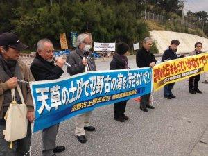 辺野古新基地反対の横断幕を持ち、座り込む市民と連携する思いを伝える熊本県連絡協議会のメンバーら=16日午前、名護市のキャンプ・シュワブゲート前