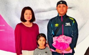 1万人目の入場者となった桃原克也さん(右)と妻の綾乃さん(左)、花帆ちゃん=17日、那覇市・県立博物館・美術館