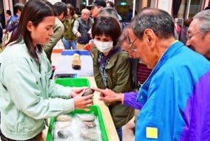 公開された文化財を説明する市教委職員(左)と物珍しそうに見入る参加者ら=19日、名護市・労働福祉センター