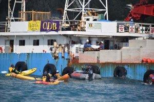 コンクリートブロックを載せた大型クレーン船に作業員がおり、抗議するカヌーに乗った市民ら=7日午前、名護市辺野古沖