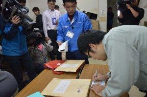国地方係争処理委員会へ審査申出書の発送手続きをする沖縄県職員(右)=14日午前11時37分、県庁