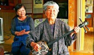 夫の故安友さんの三線を手に背筋を伸ばす小那覇ツルさんと次男の妻郁子さん=今帰仁村の自宅