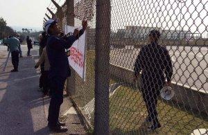 「県民弾圧を許さない」などと書かれた横断幕をフェンスに張り付けて新基地建設に抗議する市民ら=21日、名護市の米軍キャンプ・シュワブゲート前