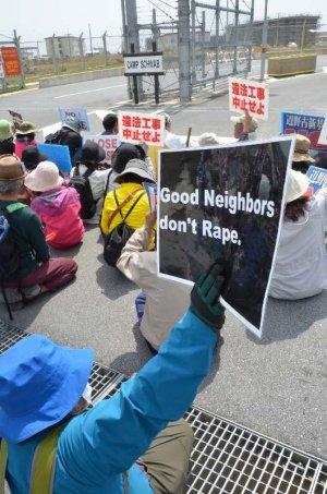 「良き隣人はレイプしない」と抗議するプラカードを持って座り込む市民=23日午前11時20分、名護市辺野古の米軍キャンプ・シュワブゲート前