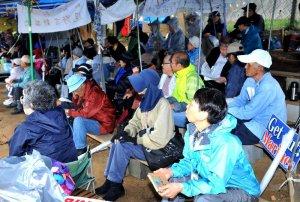 抗議集会で弁士の話に耳を傾ける市民ら=24日、名護市・米軍キャンプ・シュワブゲート前