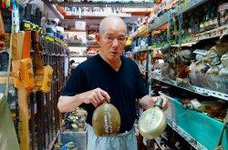 沖縄戦の遺留品が並ぶ国吉勇さんの資料館。「日本兵の水筒は茶色が陸軍、白っぽいのが海軍のもの」=那覇市楚辺