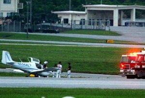 前脚が破損した状態で滑走路に停止する2人乗りプロペラ機「リバティーXL-2」(左側)。米軍の消防車両(右側)が出動した=10日午後6時41分、米空軍嘉手納基地(読者提供)