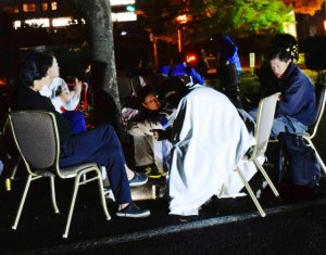 未明の地震後、ホテルの駐車場に避難した宿泊客ら=16日午前2時半ごろ、熊本市中央区(山城響撮影)